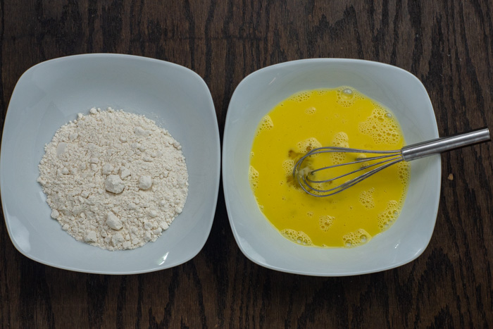 White bowls with flour in one and egg in another with a wire whisk on a wooden surface