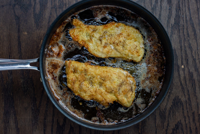 Breaded chicken cooking in a skillet on a wooden surface