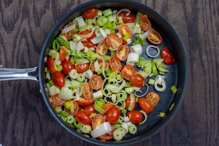 Sliced leek and tomato in a skillet on a wooden surface
