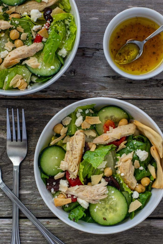 Two bowls of Greek chicken salad next to a smaller bowl of dressing with a spoon and a fork next to the bowls all on a wooden surface (vertical)