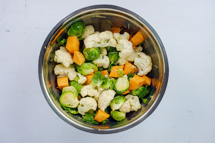 Coated raw vegetables in a stainless steel bowl on a white surface