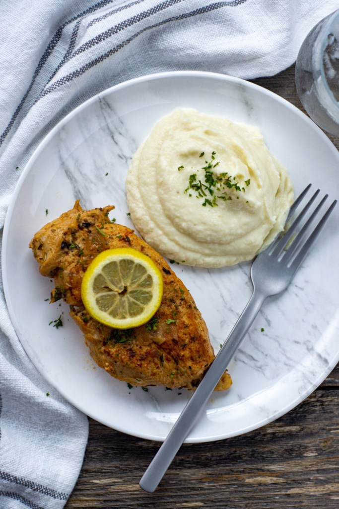 Lemon-Garlic chicken from the instant pot pressure cooker topped with a slice of lemon next to mashed potatoes on a white and grey marbled plate with a stainless steel fork on top of a white and grey napkin on a wooden surface (vertical)
