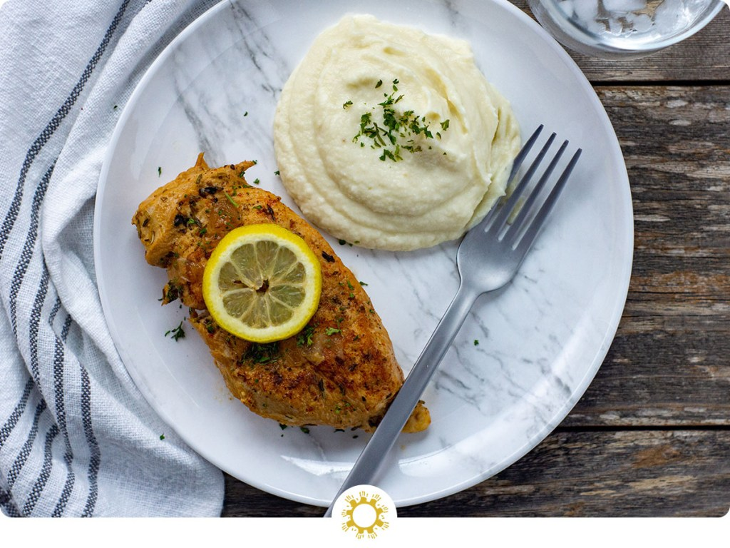 Lemon-Garlic chicken from the instant pot pressure cooker topped with a slice of lemon next to mashed potatoes on a white and grey marbled plate with a stainless steel fork on top of a white and grey napkin on a wooden surface (with logo overlay)