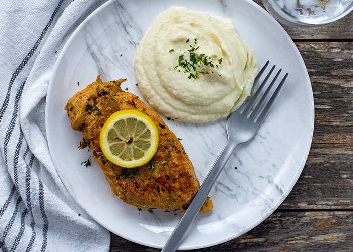 Lemon-Garlic chicken from the instant pot pressure cooker topped with a slice of lemon next to mashed potatoes on a white and grey marbled plate with a stainless steel fork on top of a white and grey napkin on a wooden surface