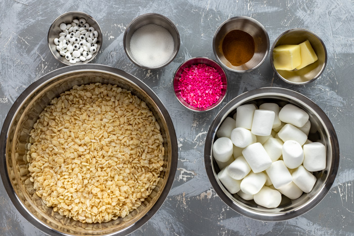 Ingredients for Sprinkle Rice Krispies in stainless steel bowls on a gray and white surface