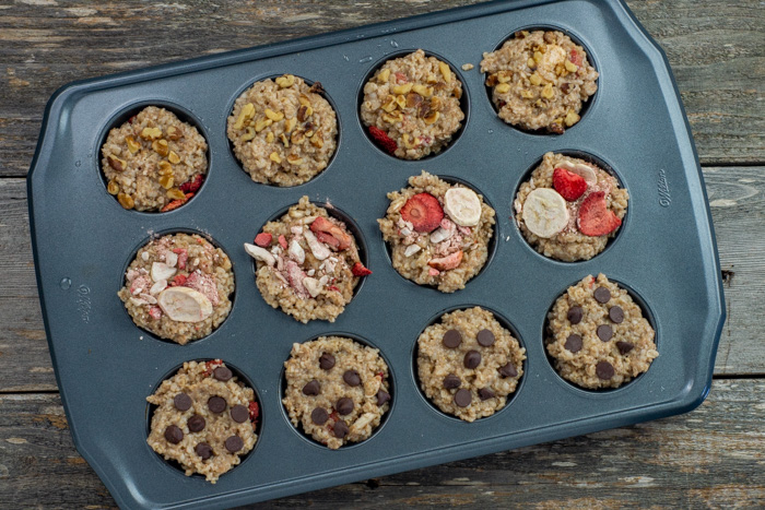 Cooked oatmeal with toppings in a muffin tin on a wooden surface