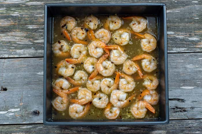 Roasted shrimp in a square metal baking dish full of butter and seasonings on a wooden surface