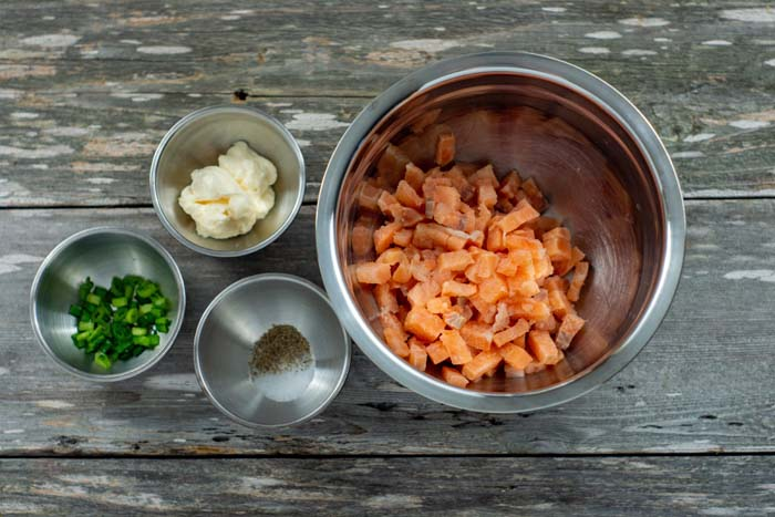 Ingredients for salmon cakes in stainless steel bowls on a wooden surface