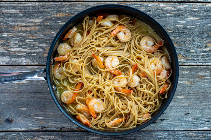 Cooked shrimp with cooked pasta noodles in a skillet on a wooden surface