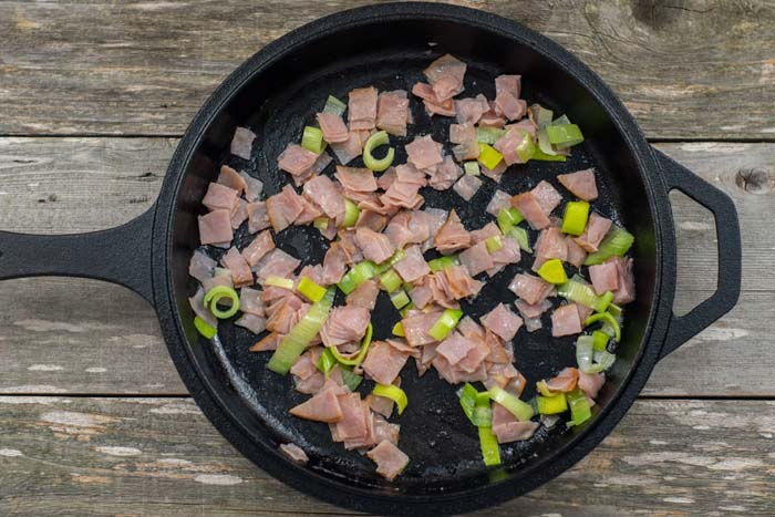 Diced ham and leeks in a cast iron skillet on a wooden surface