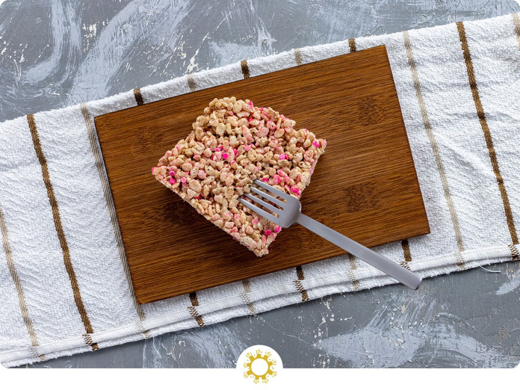 Square piece of sprinkled rice krispies on a bamboo platter with a stainless steel fork on a white and brown towel all on a grey and white surface (with logo overlay)