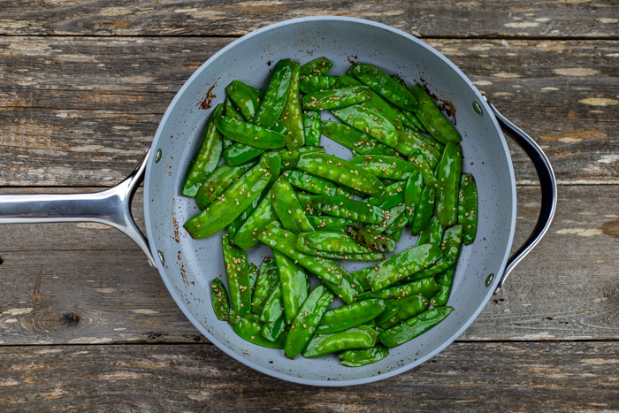 Toasted snow peas sprinkled with sesame seeds in a skillet on a wooden surface