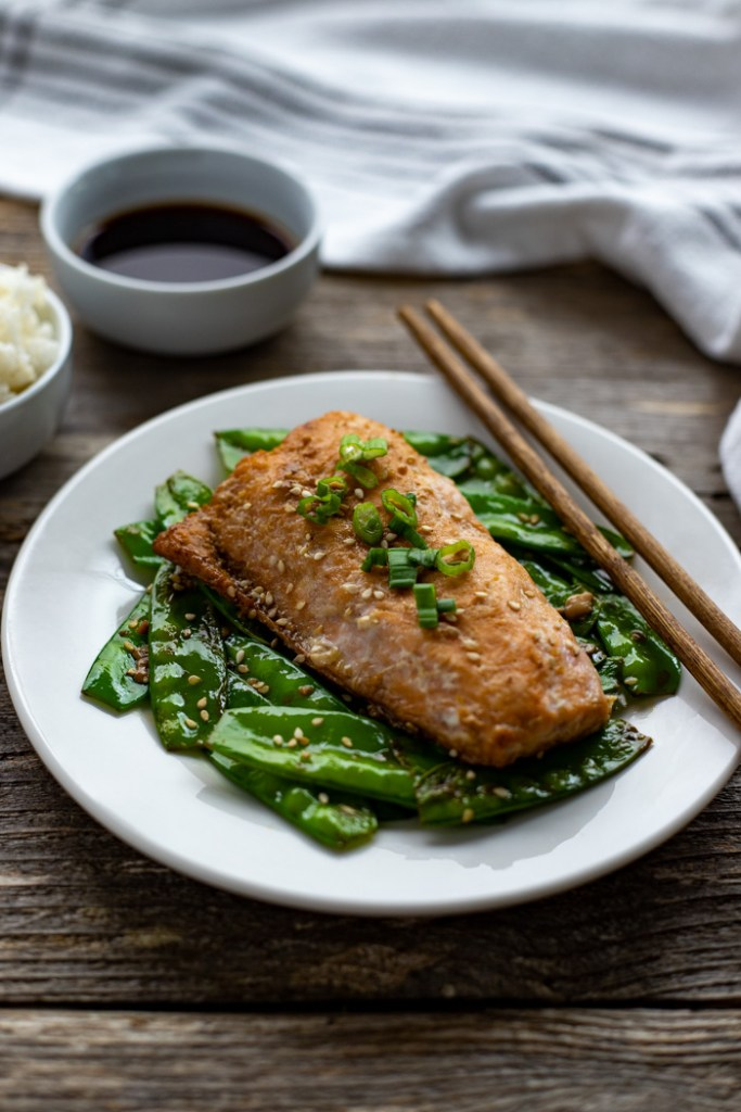 Orange ginger salmon topped with sliced green onion with toasted snow peas and wooden chopsticks on a round white place with a bowl of white rice and orange-ginger sauce behind next to a white towel all on a wooden surface (vertical)