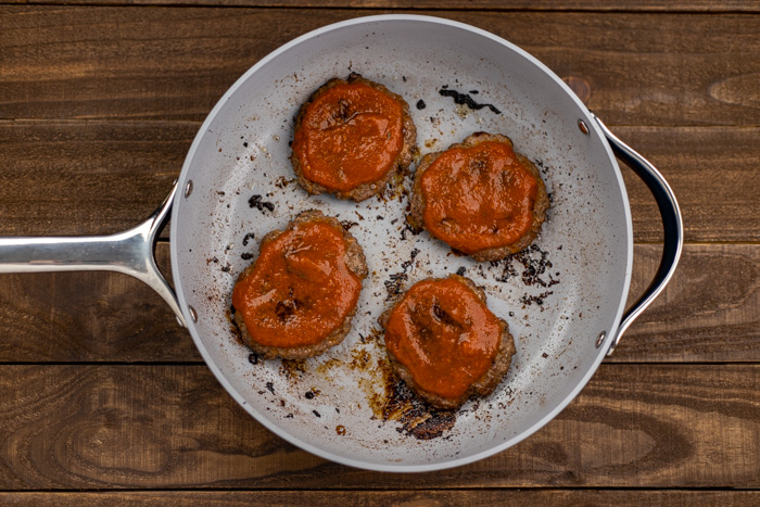 4 burger patties covered with pizza sauce in a skillet on a wooden surface