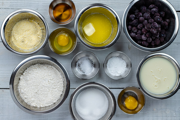 Ingredients for blueberry muffins in stainless steel bowls on a white wooden surface
