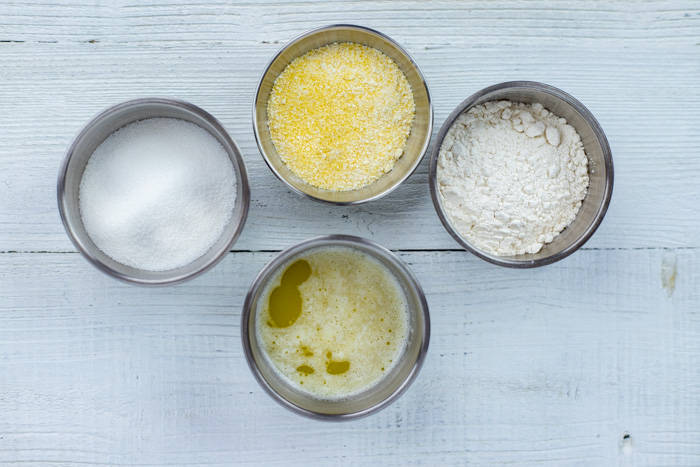 Ingredients for cornmeal struesel in stainless steel bowls on a white wooden surface