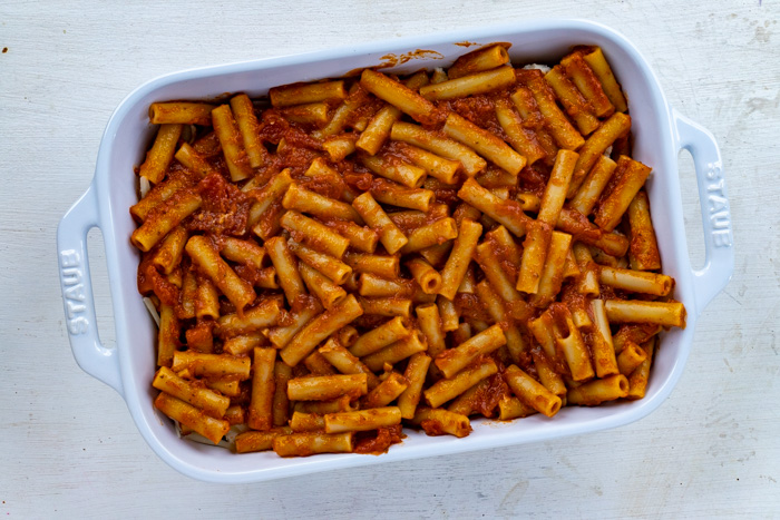 Ziti noodles covered in sauce in a white casserole dish on a white wooden surface