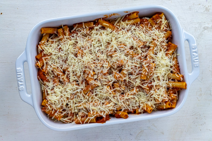 Ziti noodles covered in sauce topped with shredded cheese in a white casserole dish on a white wooden surface