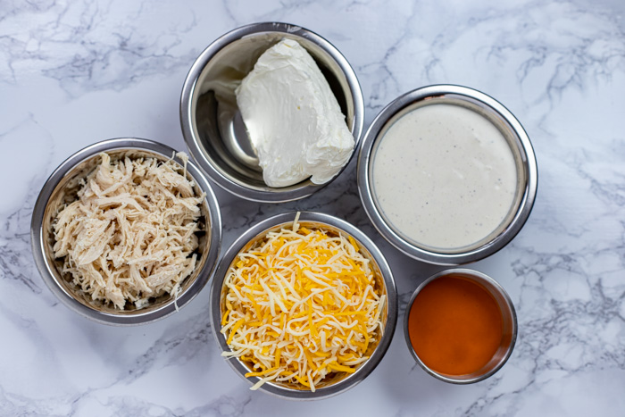 Ingredients for buffalo chicken dip in stainless steel bowls on a white and grey marbled surface