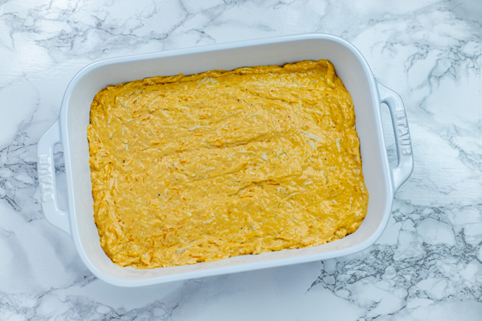Buffalo chicken dip in a white casserole dish on a white and grey marbled surface