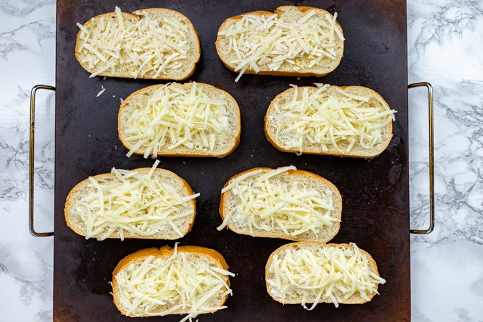 Sliced bread covered with butter, garlic powder, and shredded cheese on a baking stone on a white and grey marbled surface