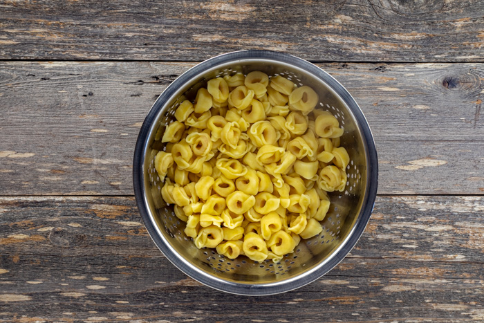 Cooked tortellini pasta in a stainless steel bowl on a wooden surface