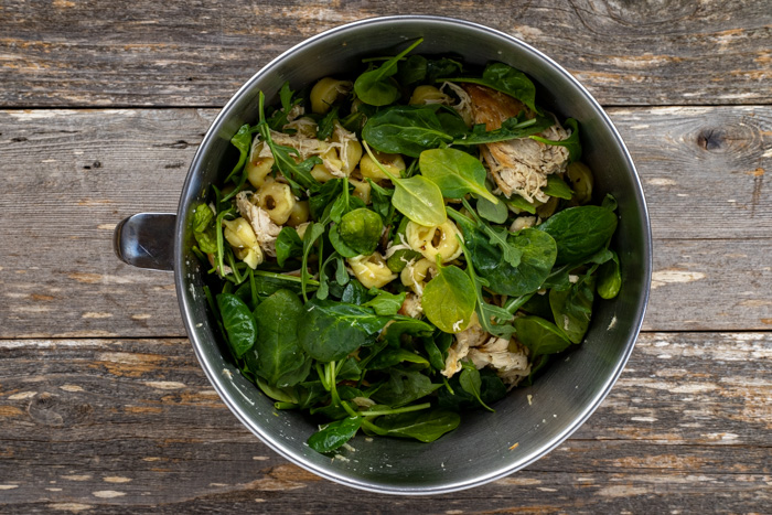 Shredded cooked chicken with cooked tortellini and lemon dressing with spinach and arugula in a stainless steel bowl on a wooden surface