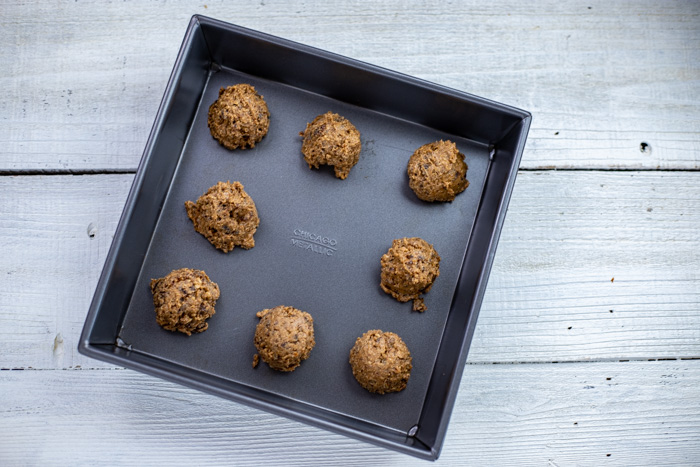 Almond-date energy balls on a metal tray on a white wooden surface