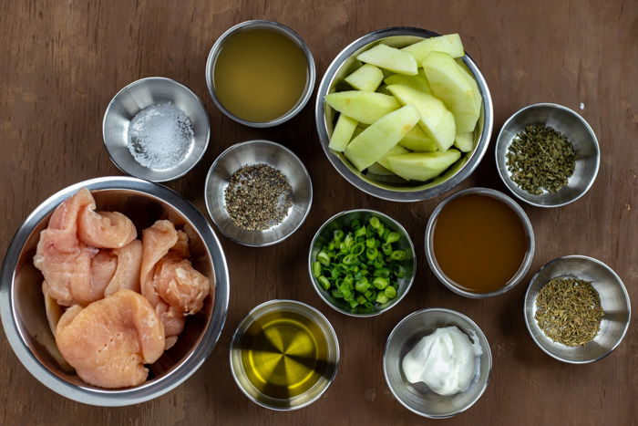 Ingredients for apple cider chicken in stainless steel bowls on a wooden surface