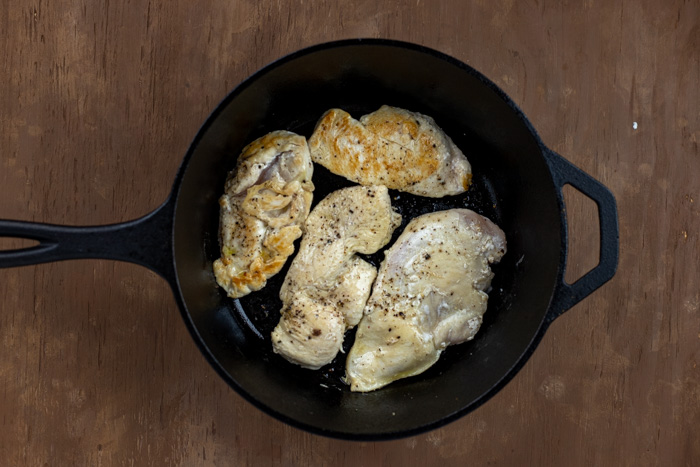 Cooked chicken in a cast-iron skillet on a wooden surface
