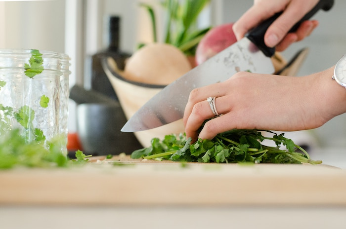 Woman's hand using a chef knife to cut fresh herbs