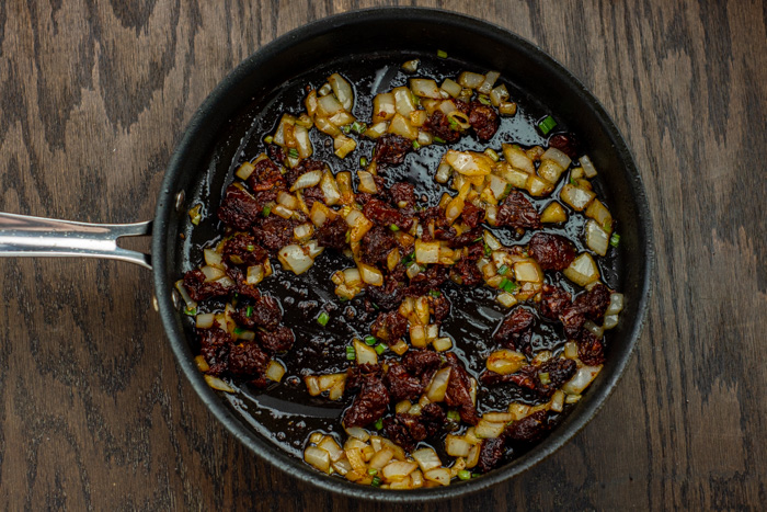 Sun-dried tomatoes and onions in a skillet on a wooden surface