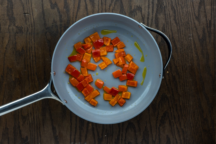 Diced red pepper cooked in oil in a skillet on a dark wooden surface
