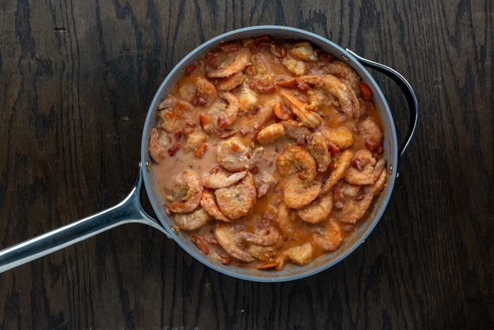 Cooked red pepper and coated shrimp with diced tomatoes and heavy cream in a skillet on a dark wooden surface