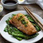 Orange ginger salmon topped with sliced green onion with toasted snow peas and wooden chopsticks on a round white place with a bowl of white rice and orange-ginger sauce behind next to a white towel all on a wooden surface (with title overlay)