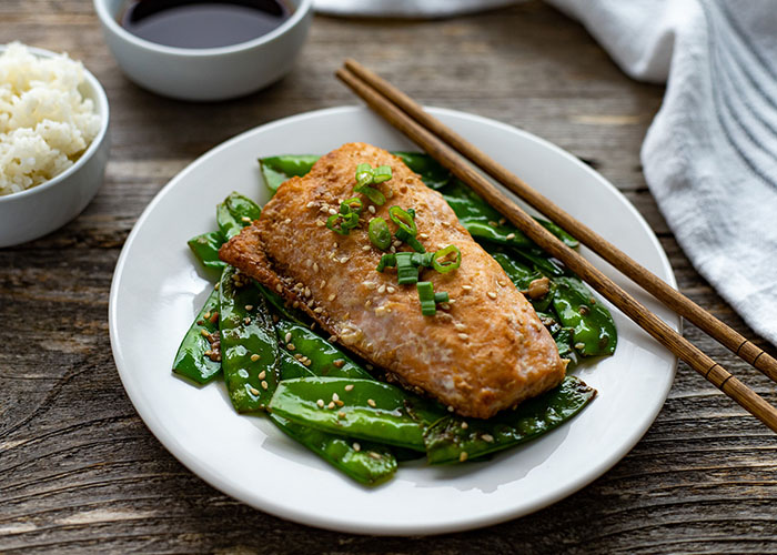 Orange ginger salmon topped with sliced green onion with toasted snow peas and wooden chopsticks on a round white place with a bowl of white rice and orange-ginger sauce behind next to a white towel all on a wooden surface