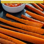 Roasted carrots on a baking sheet with a small round bowl of smoky ketchup on a grey placemat on a wooden surface (with title overlay)