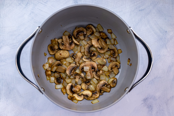 Diced onion and mushrooms in a large pot on a white and blue surface
