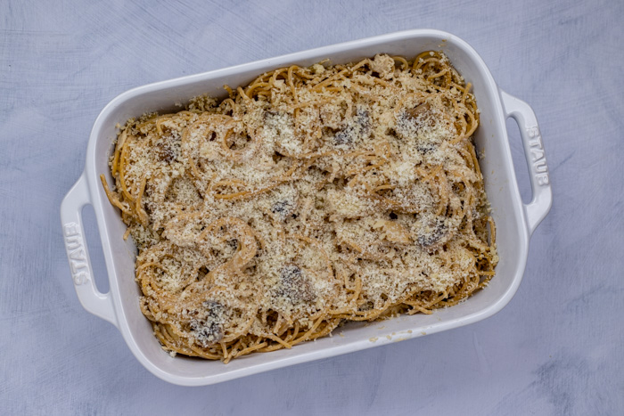 Chicken tetrazzini and noodles topped with panko and parmesan cheese in a white casserole dish on a white and blue surface