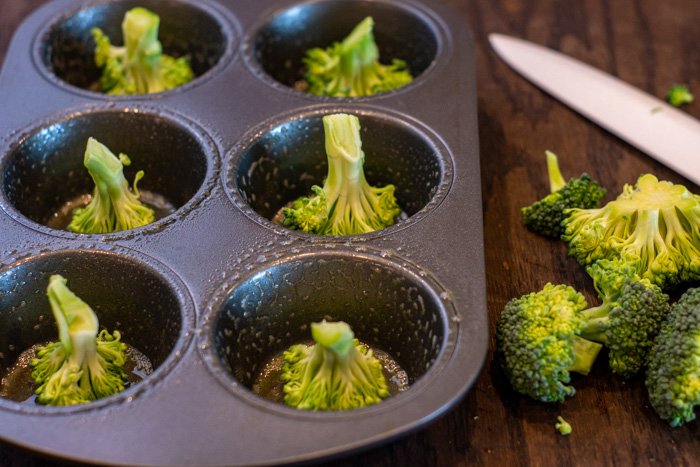 Broccoli pieces in a muffin pan with extra broccoli and a ceramic knife next to the pan all on a wooden surface