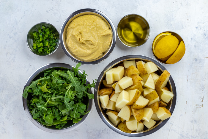 Ingredients for warm potato salad with hummus in stainless steel bowls on a white surface