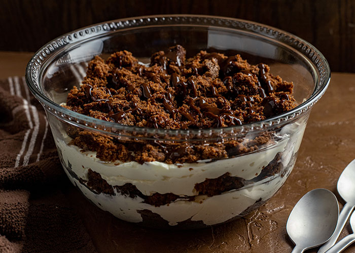 Brownie cheesecake trifle drizzled with hot fudge topping in a glass trifle bowl next to a stainless steel spoon on a wooden surface