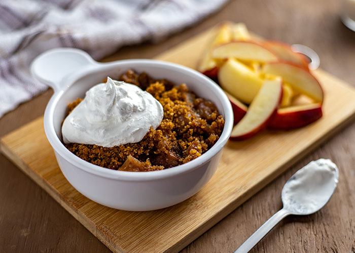 Slow cooker apple crumble topped with whipped cream in a round white bowl next to sliced apples on a bamboo tray with a stainless steel spoon in front and a white and brown towel behind all on a wooden surface