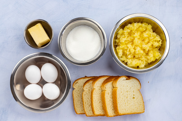 Ingredients for pineapple bread casserole in stainless steel bowls on a white surface