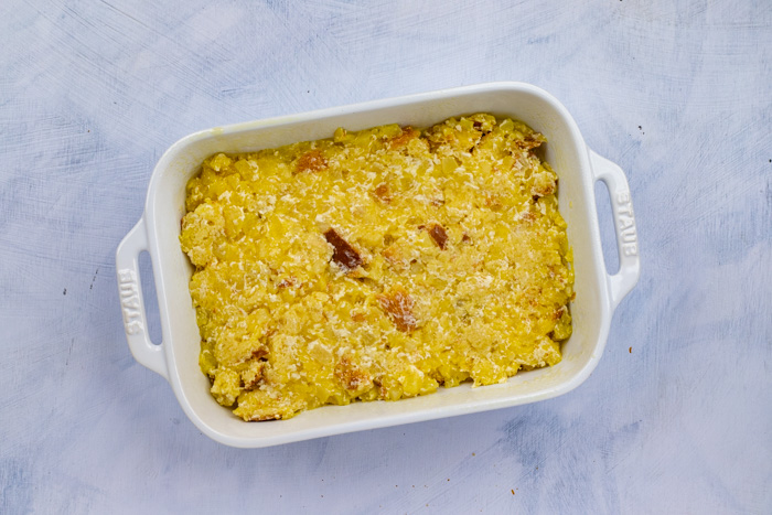 Pineapple bread casserole in a white baking dish on a white surface