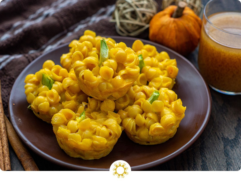 Mac and cheese bites with pumpkin stacked on a round brown pan with a glass of pumpkin juice and fall decor behind all on a wooden surface (with logo overlay)