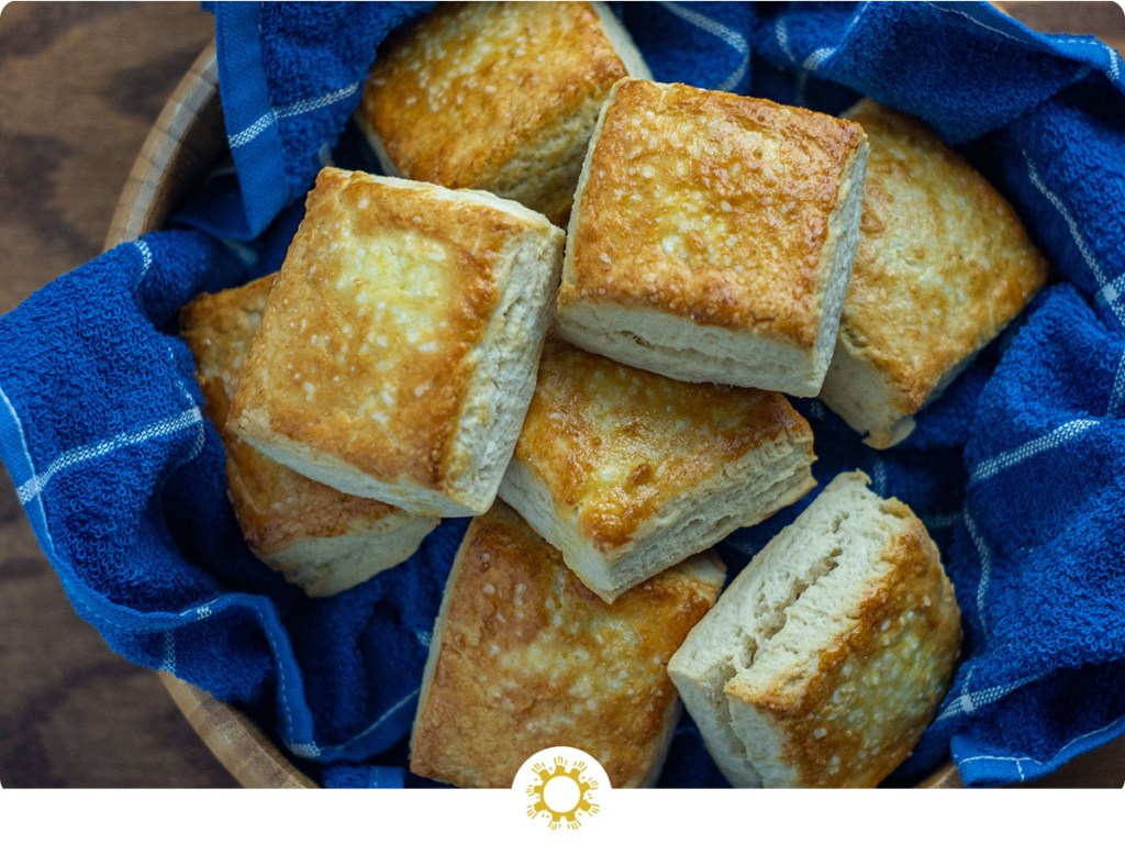 Buttermilk biscuits in a wooden bowl lined with a blue towel (with logo overlay)