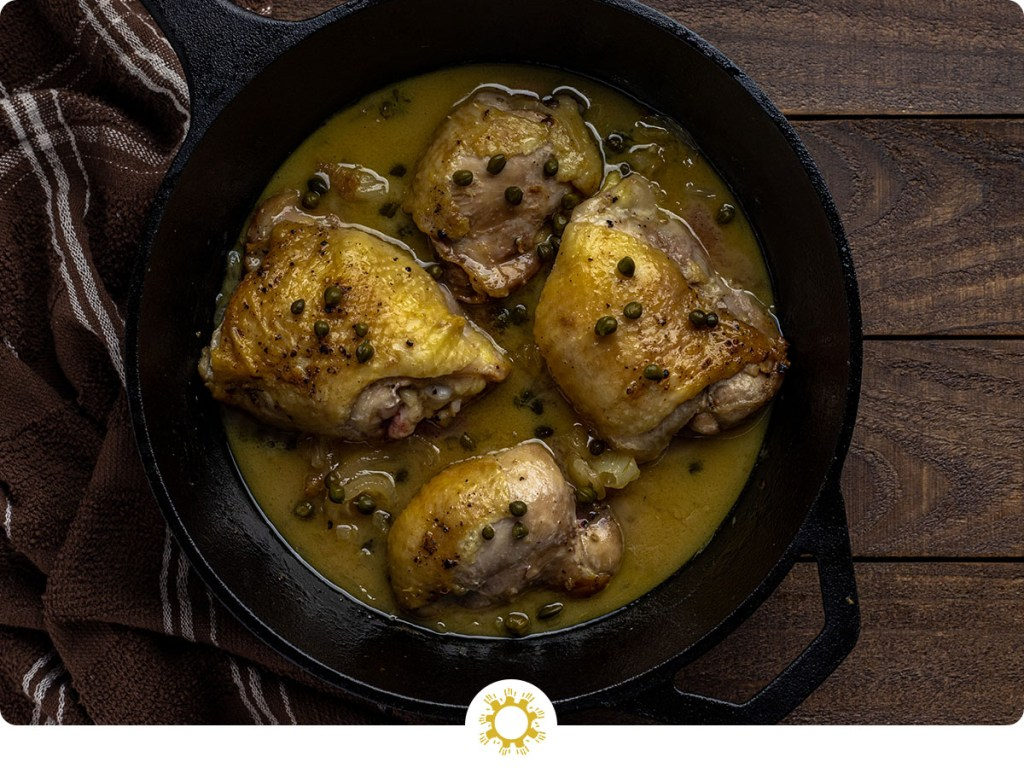 Chicken thighs with dairy-free creamy mustard sauce in a cast-iron skillet next to a brown and white towel all on a wooden surface (with logo overlay)