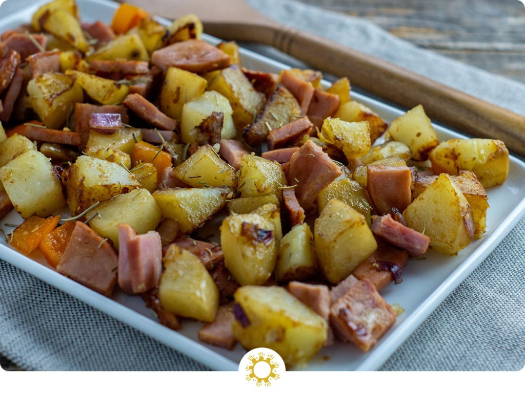 Country Ham Hash Breakfast on a square white tray next to a wooden spatula on a grey placemat all on a wooden surface (with logo overlay)