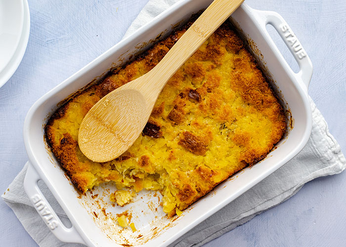 Cooked pineapple bread casserole in a white rectangular baking dish with some removed from the corner with a wooden spoon on top of a white towel with white plates behind all on a light blue surface
